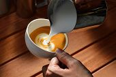 picture of latte  - Making of cafe latte art on wooded table - JPG