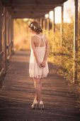 stock photo of tied hair  - Pretty young girl with blond hair tied with a flower crown and white dress - JPG