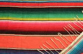 stock photo of mexican fiesta  - Traditional Mexican fiesta poncho rug in bright colors background with copy space - JPG