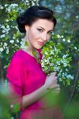 picture of cherries  - young beautiful brunette woman in pink dress in blooming cherry tree garden - JPG