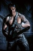 image of man chainsaw  - Handsome muscular man with a chainsaw over dark grunge background - JPG