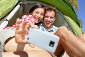 image of two women taking cell phone  - Camping couple in tent taking selfie using smartphone - JPG