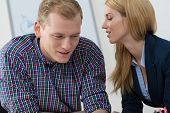 image of coworkers  - Two coworkers gossip at office about coworkers - JPG