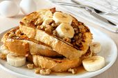 stock photo of french toast  - Plate of delicious French toast with bananas walnuts and dripping maple syrup - JPG