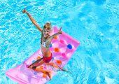 stock photo of mattress  - Child swimming on inflatable beach mattress - JPG