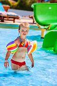 stock photo of rebs  - Child in reb bikini with armbands playing in swimming pool - JPG