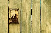 picture of mailbox  - Old rusty mailbox is hanging on old wooden fence with cracks - JPG