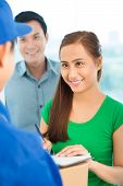 stock photo of confirmation  - Smiling young Vietnamese couple signing delivery confirmation - JPG