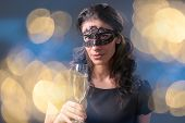 image of masquerade  - Sensual woman wearing black masquerade carnival mask at party holding a glass with champagne over holiday bokeh background - JPG