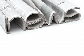 stock photo of conduction  - Stacks of modern newspapers composed in form of word NEWS on white background - JPG