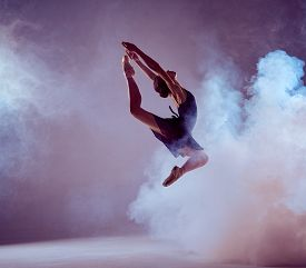 picture of  dancer  - young ballet dancer jumping on a lilac background. Ballerina is wearing in blue dress and pointe shoes. The outline shooting - silhouette of girl with smoke effect ** Note: Soft Focus at 100%, best at smaller sizes - JPG