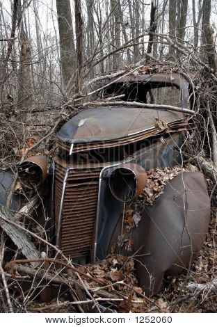 Picture or Photo of A 1937 studebaker sedan delivery abandoned and left to rust in the woods.