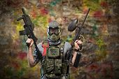 Постер, плакат: Handsome paintball gamer with guns in camouflage uniform