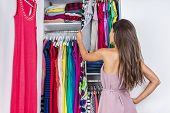 Постер, плакат: Home woman choosing her fashion outfit in dressing room Woman in bedroom walk in organized closet l