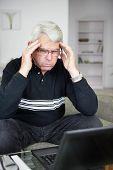 Retrato de un hombre preocupado tratando de concentrarse frente a una computadora portátil