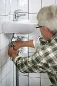 A man undoing the siphon of a washbasin