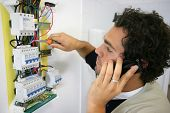 Man working on a circuit breaker and phoning