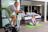 picture of 55-60 years old  - Portrait of a senior man making exercise bike and a senior woman doing yoga - JPG