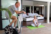 Portrait of a senior man making exercise bike and a senior woman doing yoga