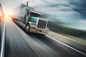 stock photo of trucks  - Big freight truck speeding on freeway at sunset - JPG