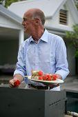 Retrato de un senior hombre preparar brochetas de pescado en una plancha