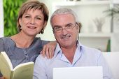 picture of reading book  - Senior woman reading a book near a senior man - JPG