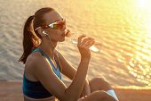 Running woman in sport sunglasses drink. Female runner with her bottle with water freshness after tr poster