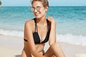 Plesant Looking Young Female In Black Swimsuit Looks Happily Aside, Being At Seaside Alone, Enjoys W poster