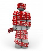 A person is wrapped up in red ribbon with the words Red Tape repeated, representing getting caught up in a mess of bureaucratic rules, regulations and procedures while trying to get something done