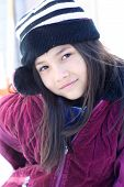 Spunky Little Girl In Winter Clothing Posing Outdoors poster