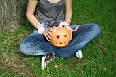 Teenager in jeans with halloween pumpkin