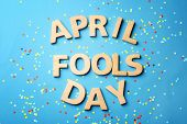 Phrase April fools day and confetti on color background poster