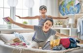 Go on an adventure! Happy family preparing for the journey. Mom and daughter are packing suitcases f poster