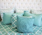 Closeup photo of teal cushions on bed