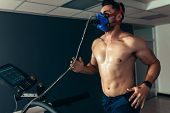 Fit And Muscular Athlete With Mask Running On Treadmill poster