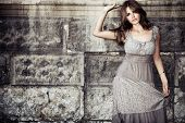 young woman in summer dress  against old stone wall, outdoor shot