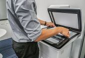 Close Up Businessman Use Printer To Scan Important And Confidential Documents In Office poster