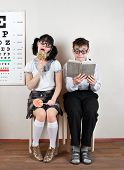 Two person wearing spectacles in an office at the doctor