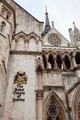 The Royal Courts of Justice (the Law Courts) Victorian Gothic exterior with sign and coat of arms, C poster
