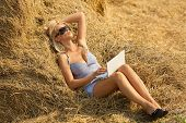 Sexy woman on laptop in hay stack on a summer day
