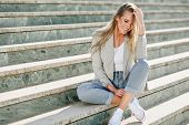 Beautiful Young Blonde Woman Smiling On Urban Steps. poster