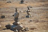 Stone cairns erected on the way in a barren landscape poster