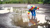 Child Walking In Wellies In Puddle On Rainy Weather poster
