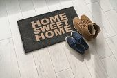 Home sweet home doormat at condo door entrance with couples pairs of shoes moving in together. women poster