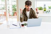 Young student man using computer laptop and notebook screaming proud and celebrating victory and suc poster