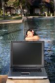 Attractive Woman Sleeping Near A Laptop By The Pool