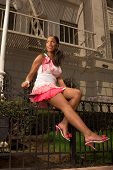 Black Woman In Pink Skirt Sitting On Forged Fence