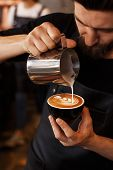 Young Smiling Male Barista Making Cappuccino. Pouring Milk For Prepare Cup Of Coffee. Latte Art. Mor poster