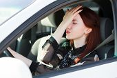 Troubles on the road, Girl hides face in hands while in a car