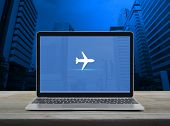 Airplane Flat Icon With Modern Laptop Computer On Wooden Table Over Office City Tower And Skyscraper poster